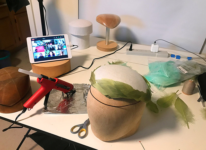 Work table with feather-covered hat in progress and a Zoom session displayed on iPad.