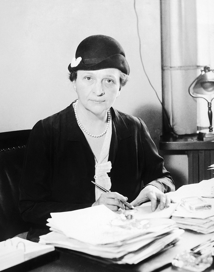 Frances Perkins, wearing a casual felt hat, working at her desk.