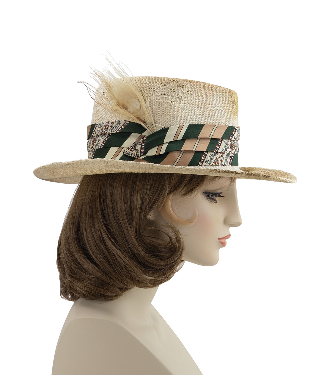 Right side view of ivory peacock feather on distressed wide-brim straw hat with green silk band, displayed on a mannequin head.