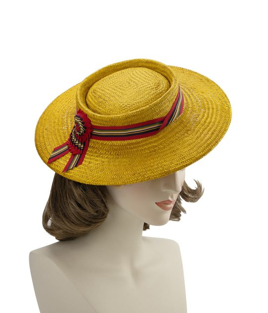 A mustard yellow straw perching boater with red striped ribbon band and nautilus cockade, displayed on a mannequin head.